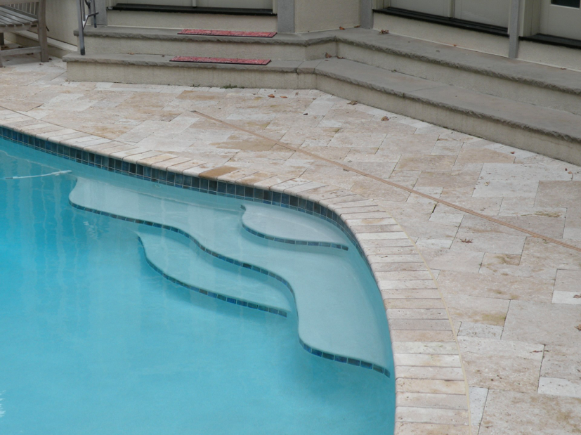 Tri-State project with 3x3 tile trim on step risers and 3x3 waterline tile. Bullnose Travertine Coping, Noche and Diamond Brite interior finish, Cool Blue.