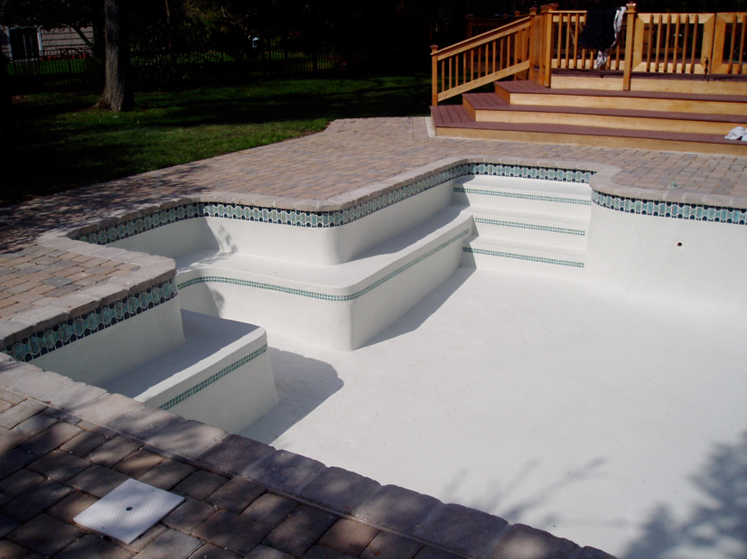 Tri-State project with 1x1 tile trim (double row) on steps and Mosiac waterline tile. Tumbled Paver Coping, Coping, Dublin Cobble 9x9 and Marblewhite Plaster interior finish. Cambridge Cobble paver deck.