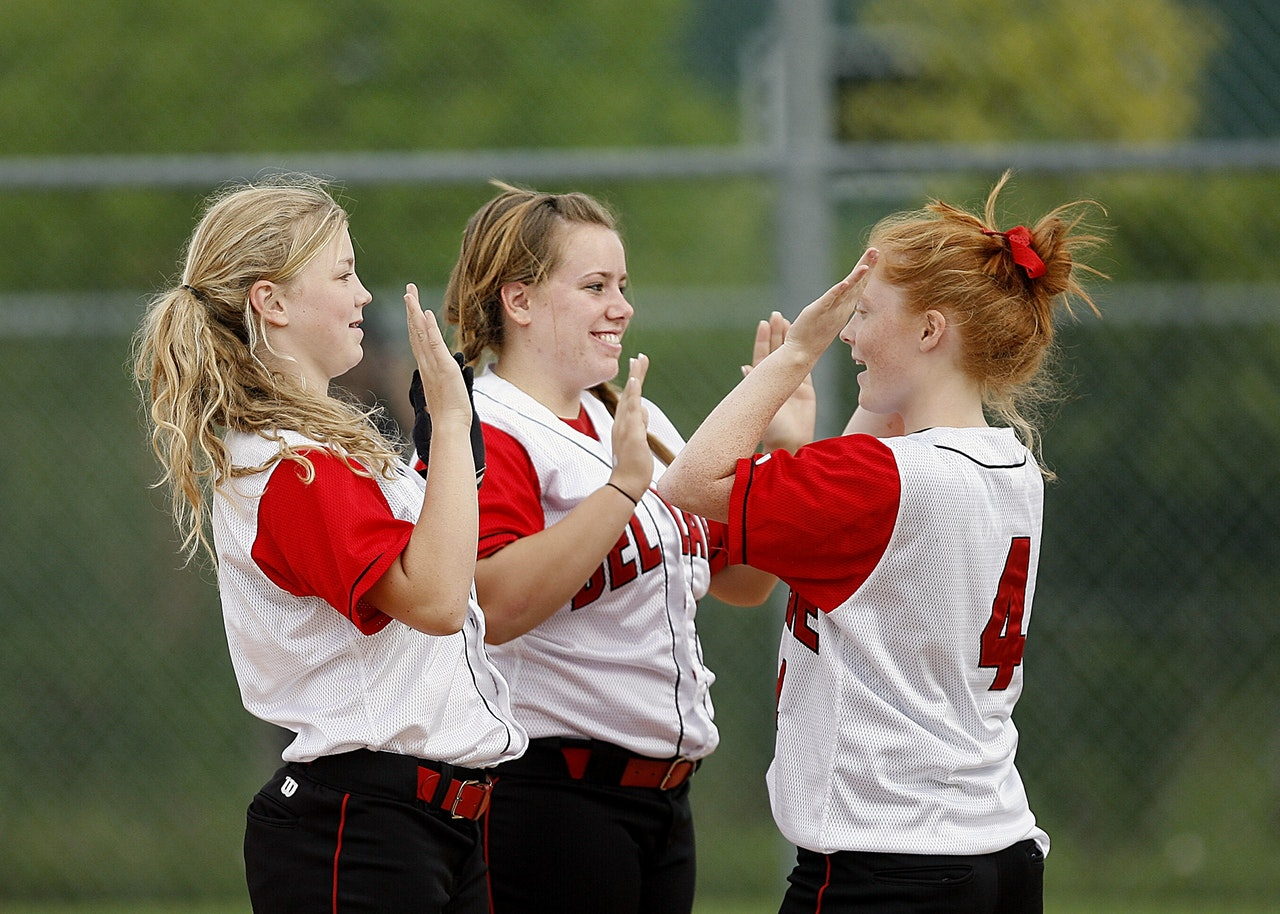 Teenage girls playing softball. Online Counseling sessions help busy teenagers get help for depression, anxiety and friend problems.
