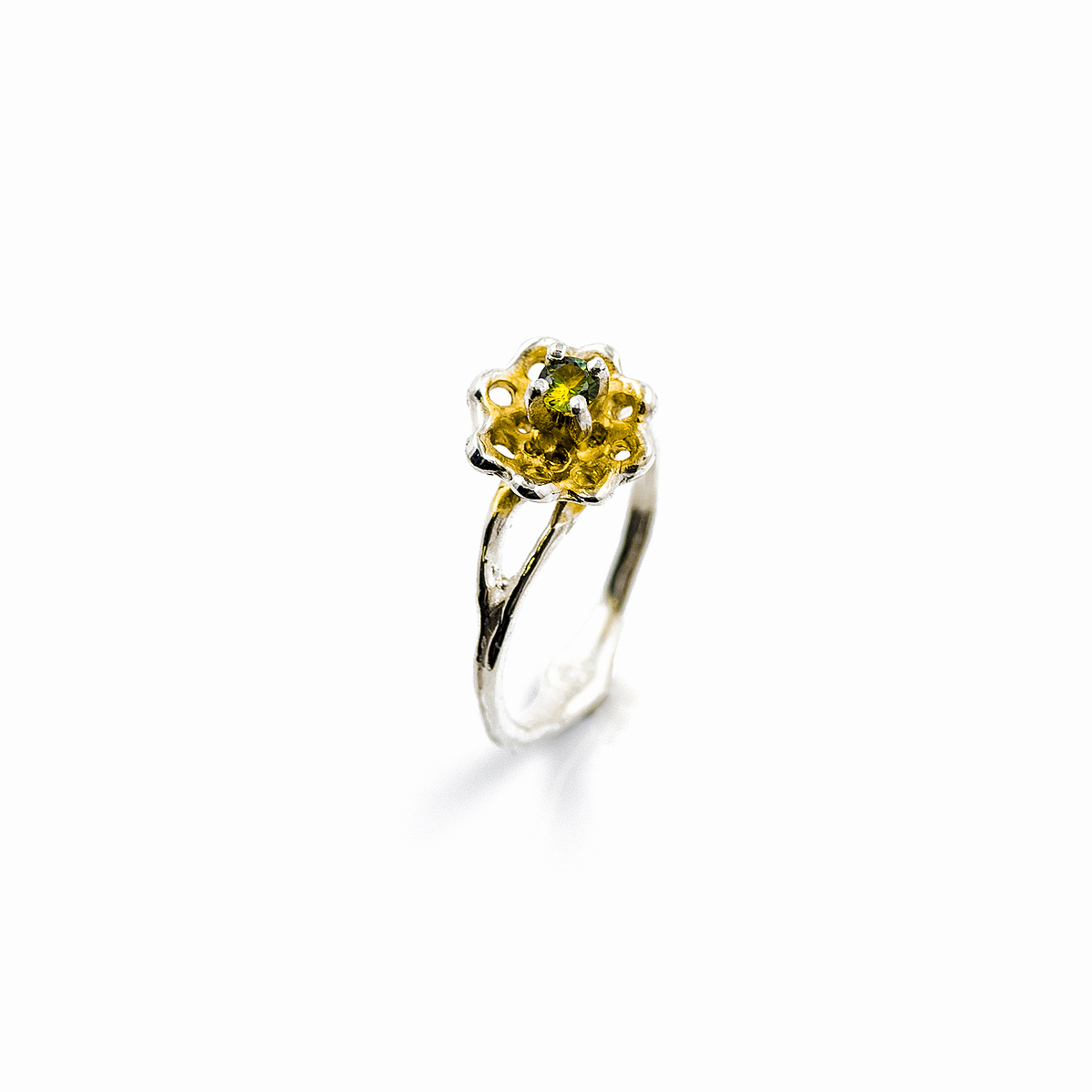 A yellow-green Australian sapphire extends from a golden surfaced silver fan.