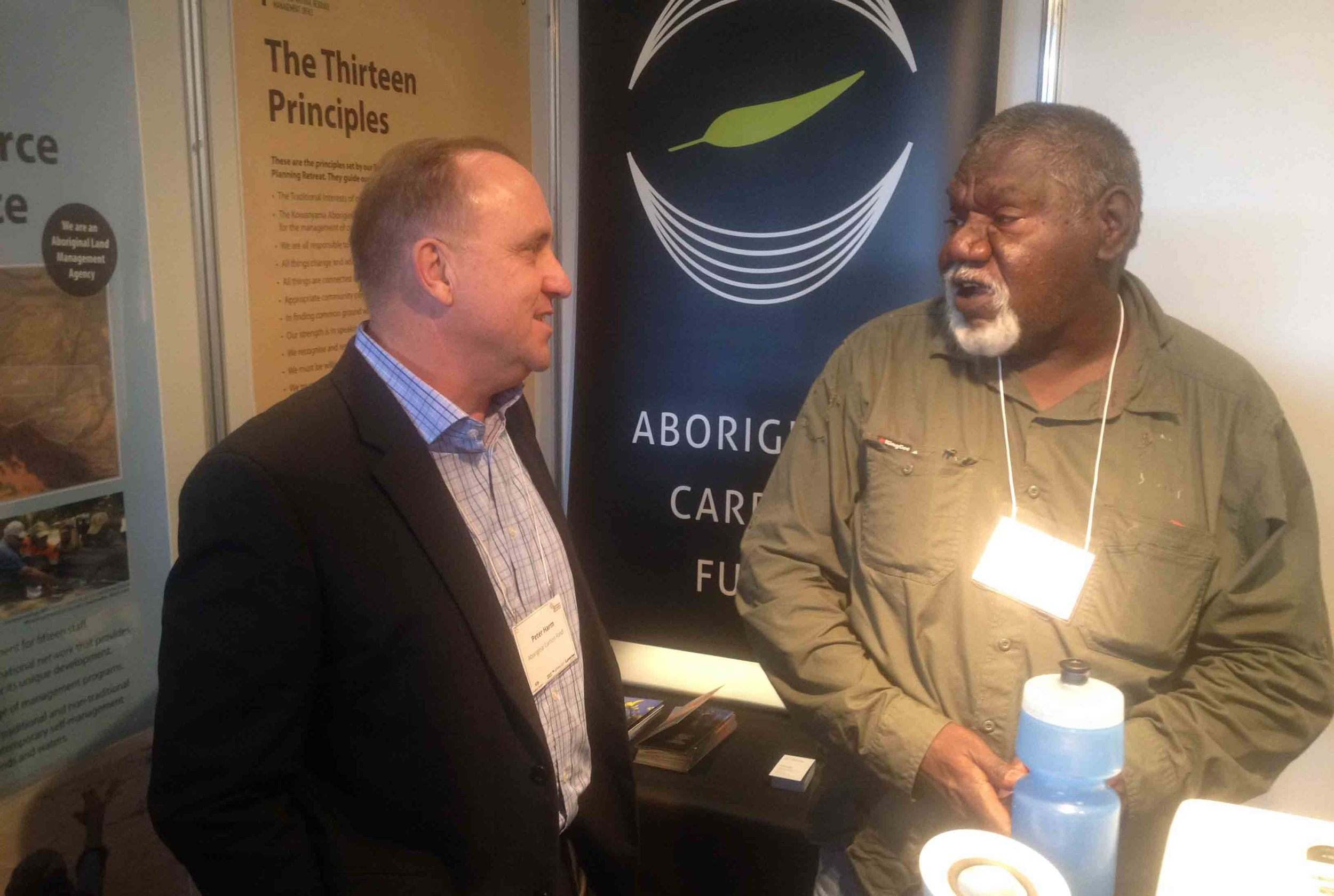Peter and John talking under the brights of the Aboriginal Carbon Fund stall