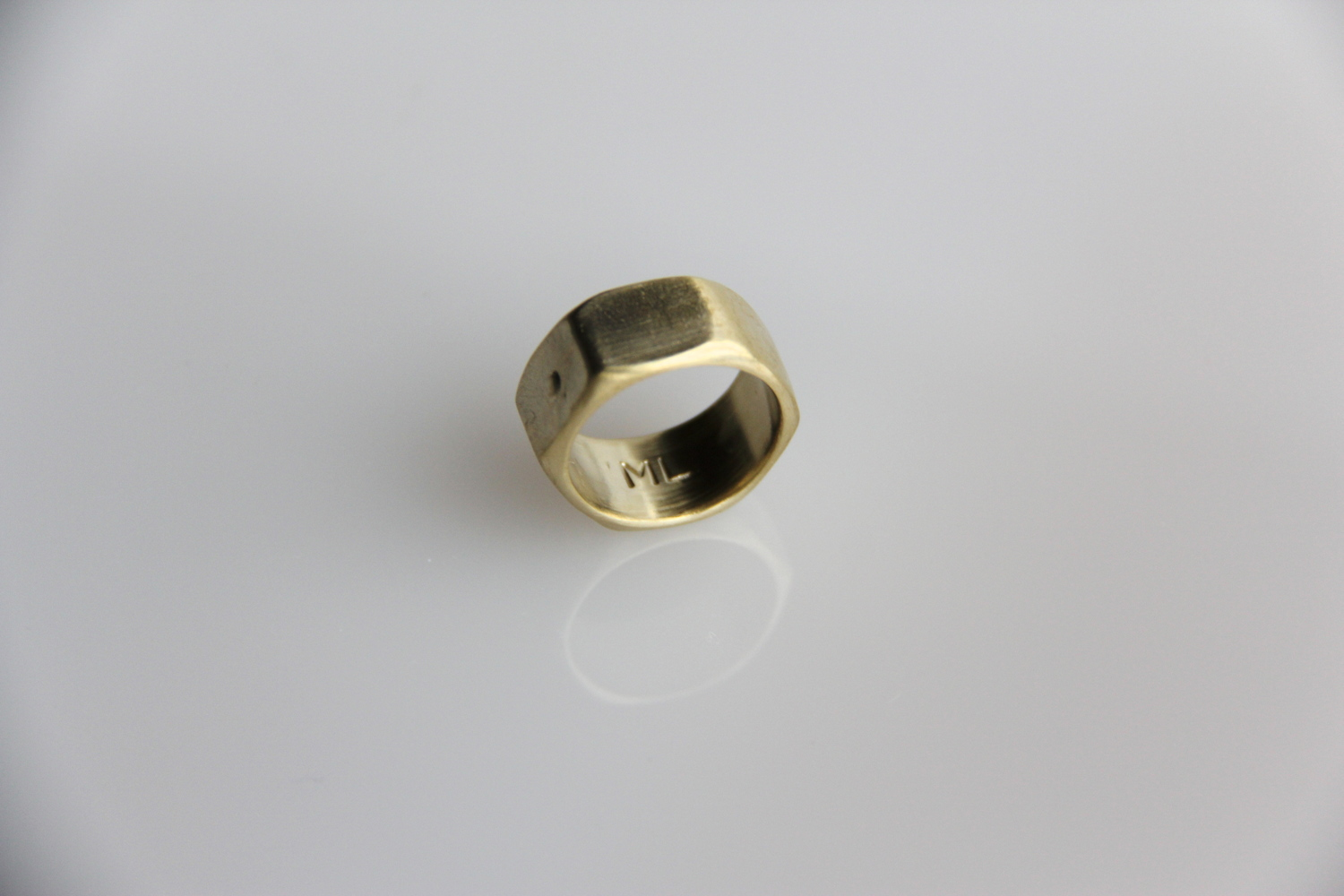 """Brass Nut Ring   The inspiration for this ring was an industrial nut and bolt. Itsdesign combines an industrial nut with the """"brass knuckle"""" weapon into one single ring band. As a wedding band or symbolic love ring, it playfully bolts you to one another—gently and powerfully all at once.  When choosing sizing, select a half size up. So if you are a size 6, then order a 6.5 ring  Matte Yellow Brass"""