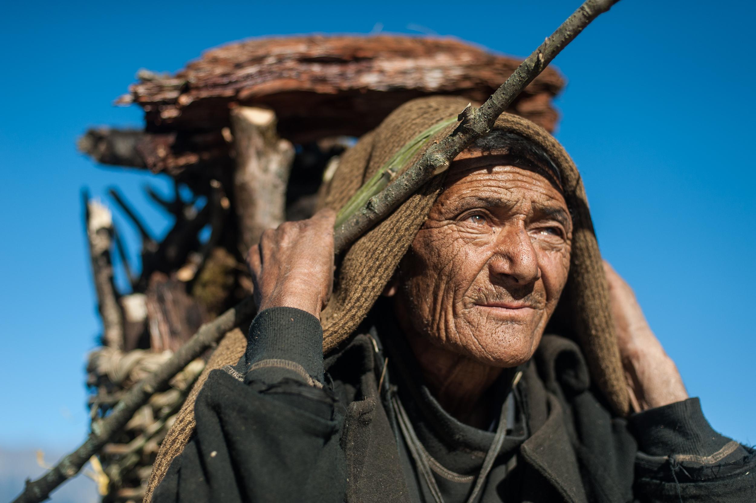 An elderly Gurung man from the Manaslu region in Nepal carries firewood.