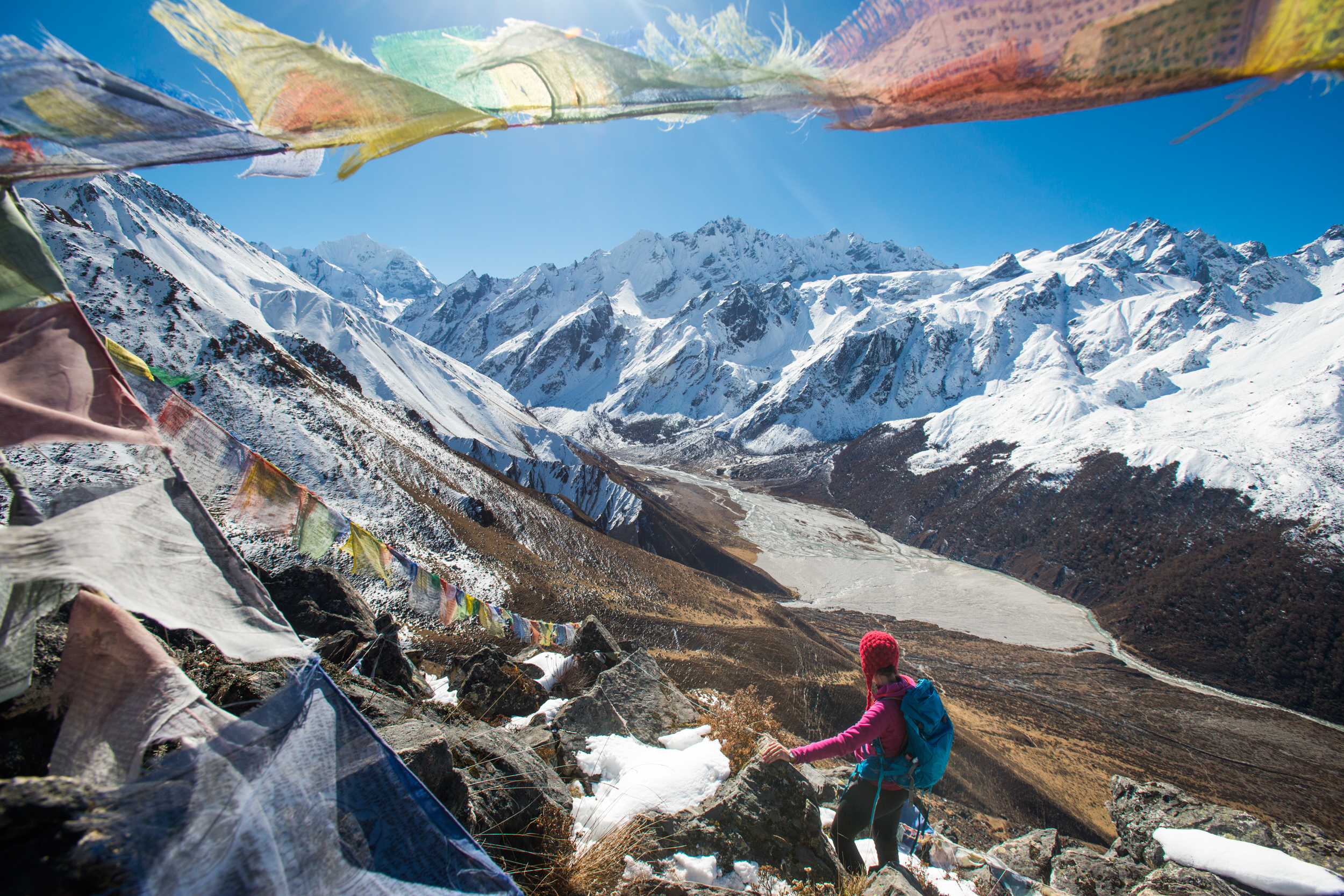 A woman trekking in the Langtang valley in Nepal stands on the top of Kyanjin Ri and looks out towards Ganchempo in the in the distance.
