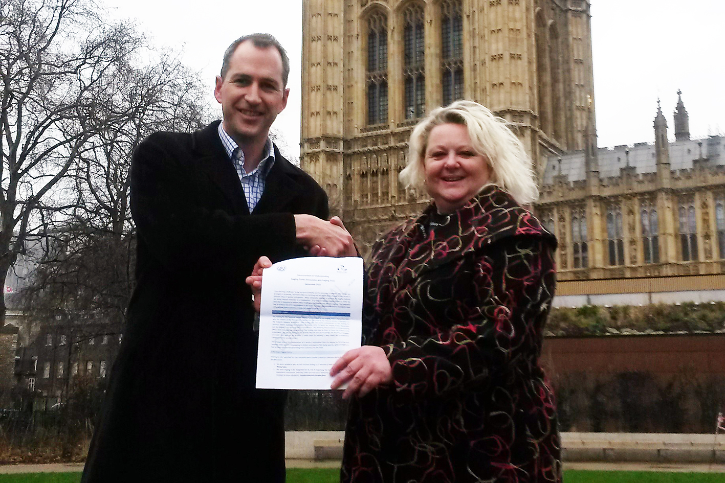 Mark Lloyd, CEO Angling Trust and Naidre Werner, Chair Angling Trades Association holding MoU agreement outside the Houses of Parliament