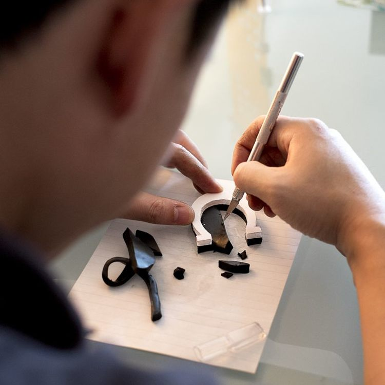 Here is a photo of me building out Dark Alice's horseshoe necklace (because I couldn't find one I could buy).  The necklace was first carved out of foam core board as a template then sculpted out and baked with Fimo sculpting clay. Spray painted later to look like metal.