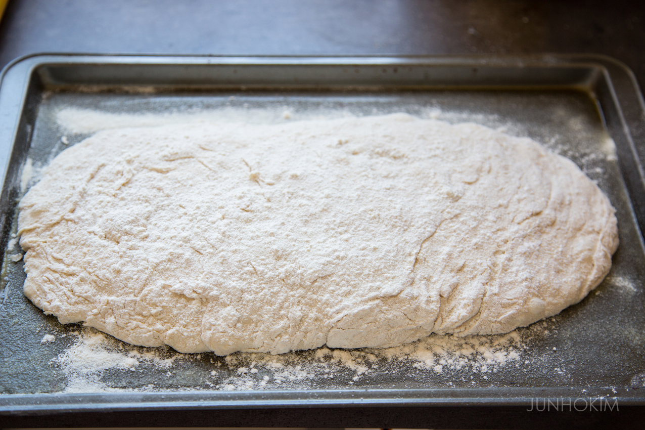 Place the dough on the pan and add flours on the top of the dough