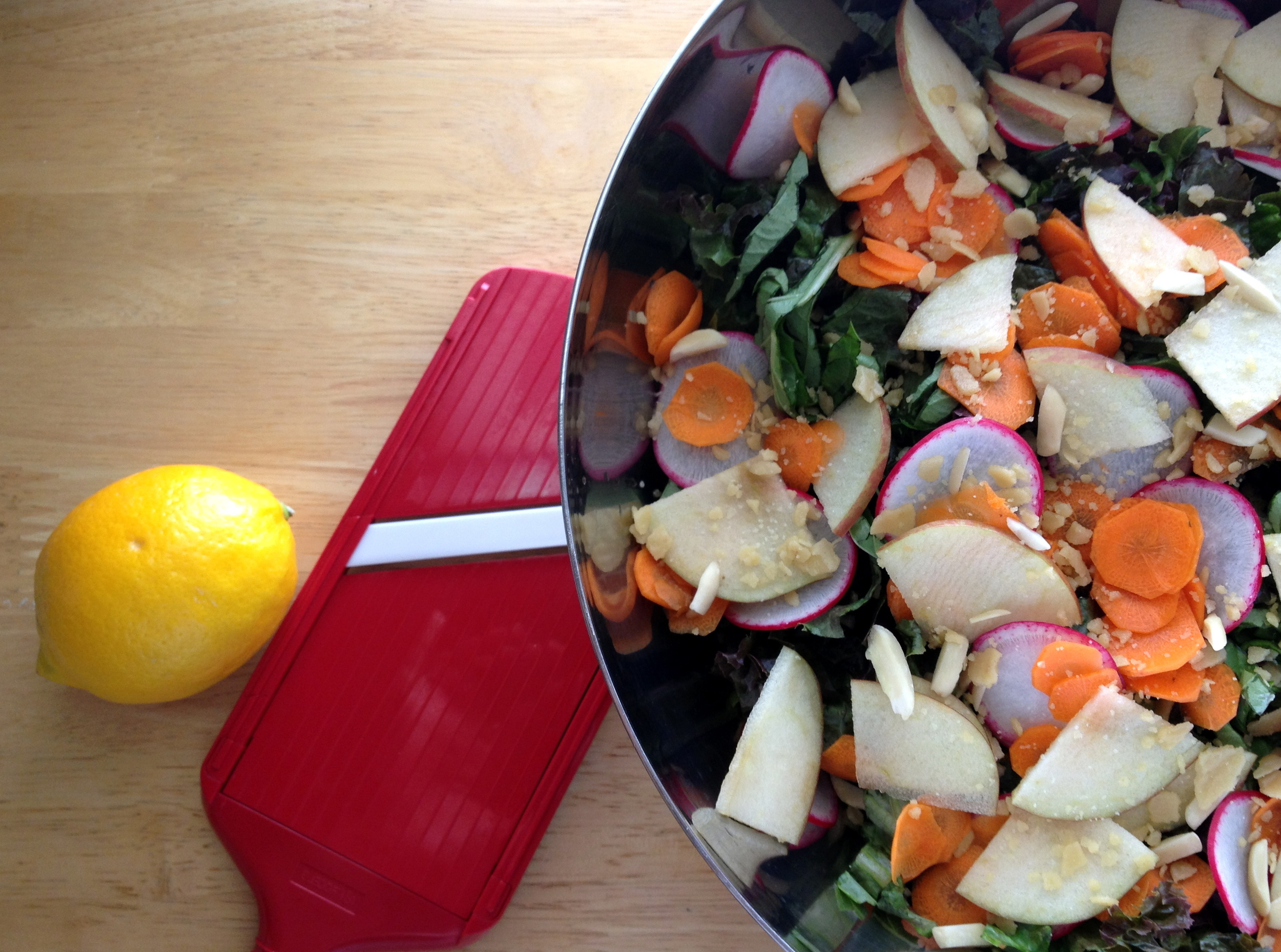 Salad with sliced carrot, pear, and radish topped with pine nut parmesan.