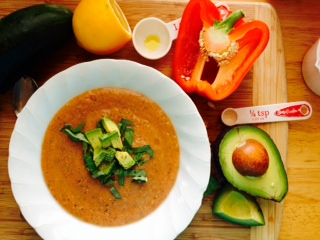 Gazpacho topped with avocado and basil.