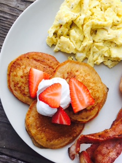 Plantain pancakes with coconut whipped cream and strawberries