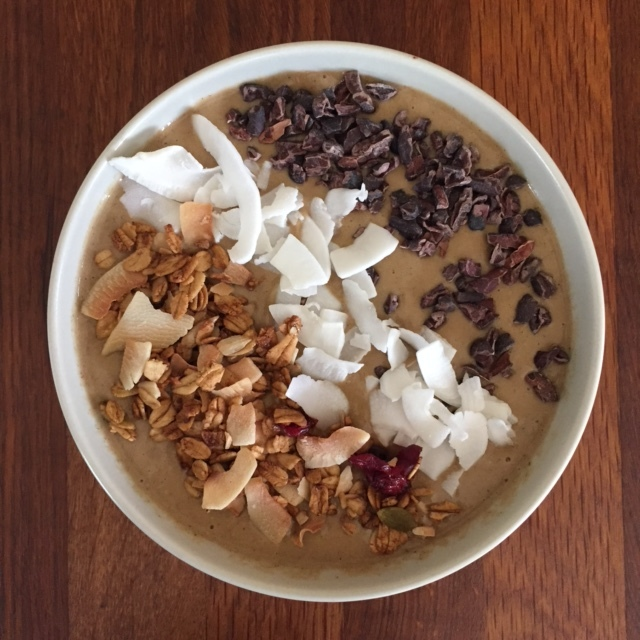 Chocolate smoothie bowl with raw cacao nibs, coconut flakes, and gluten-free coconut granola