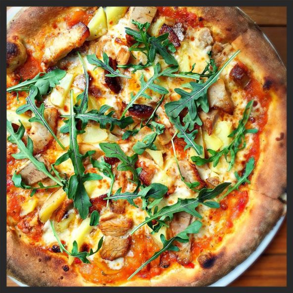 Slow Roasted Pork Pizza with heirloom tomato sauce, Fresno chilies, fingerling potatoes, and mozzarella at Michael's Genuine  | Credit: Instagram @michaelsgenuine