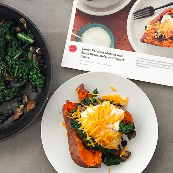 A prior box option from Plated: sweet potatoes stuffed with black beans, kale, and yogurt sauce. | Instagram @modernensemble