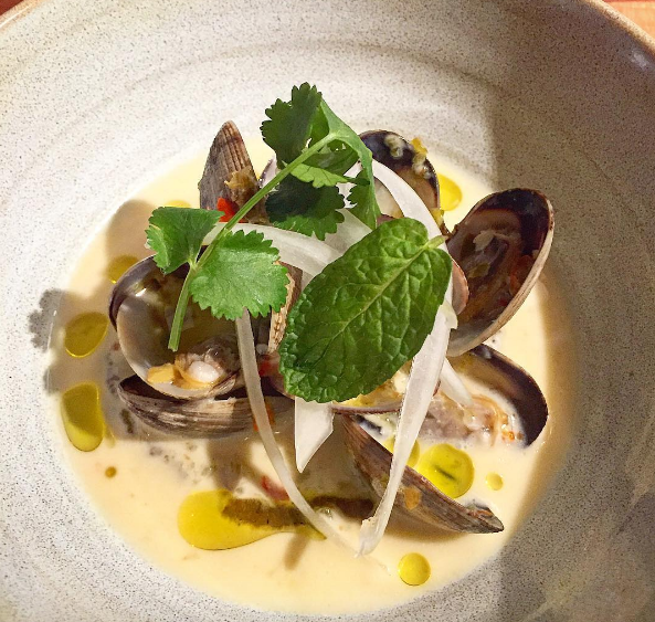 Manila clam, hot pepper jelly, coconut milk, charred yam purée, onion, cilantro & mint at Mabel Gray  | Instagram @ChefJamesRigato