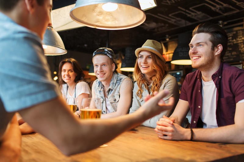 happy-friends-drinking-beer-talking-bar-people-leisure-friendship-communication-concept-group-smiling-pub-56184640.jpg