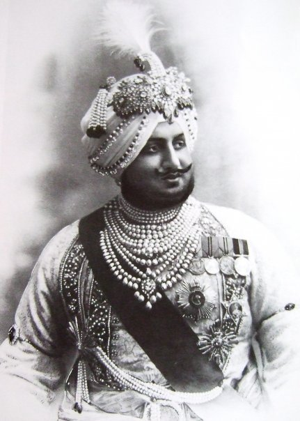 Maharaja Bhupendra Singh of Patiala. 1911. Wears an aigrette or Sarpech by Cartier and various other turban ornaments. While the front of aigrette is set with diamonds, rubies and emeralds, the back shows the intricacy of craftsmanship with foliate motifs of red, green and blue enamel. He also wears a necklace of fourteen strands of natural pearls.