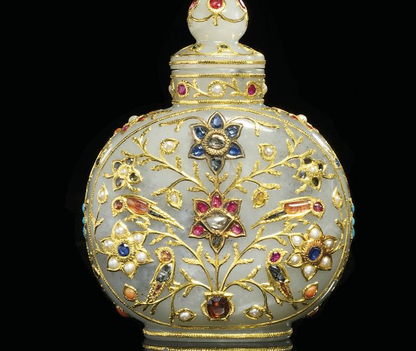 A Mughal-style gemstone-encrusted white jade scent bottle. 18th/19th century. Of flattened circular shape on a short oval foot, the cylindrical neck fitted with a screw-top cover with a knop finial, the body inlaid in gold and inset with gem stones including diamonds, rubies, sapphires and emeralds, depicting two panels on the front and back enclosing birds and blossoming branches, the sides with further blossoms.