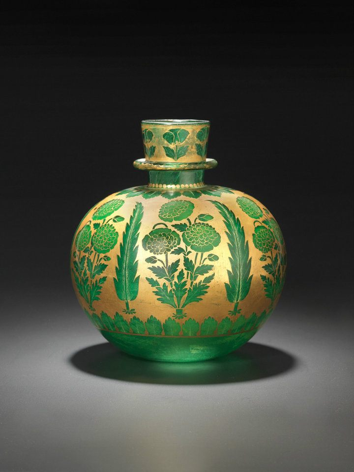 "Huqqa (water pipe) of emerald-green glass decorated with gold and yellow enamel Northern India; 1st half of 18th century.    The motif was painted ""in reserve,"" which means that the gold was largely used as the background for the motifs – poppies and cypresses along with various leaf borders. A few details, such as the ribs or little leaves, were executed in gold or yellow enamel. A special refinement is the use of enamel inside, behind the flower heads. Photo: The David Collection"