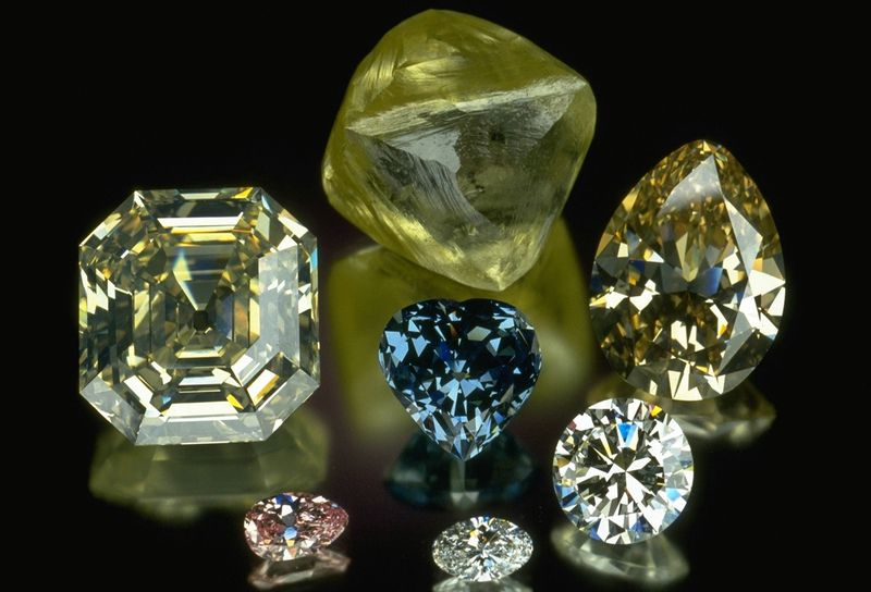 Photograph of a group of large, clear, colored diamonds from the National Gem Collection with Blue Heart diamond at its center. Photo by Chip Clark, Smithsonian National Museum of Natural History.