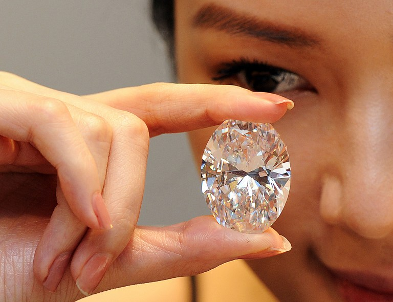 A model holds a 118.28-carat, flawless diamond dubbed the 'Magnificent Oval Diamond' during a media preview at Sotheby's Hong Kong auction house on September 19, 2013. The stone broke a world record on October 7, 2013 when it fetched more than 30 million USD on auction. Photo: Laurent FIEVET