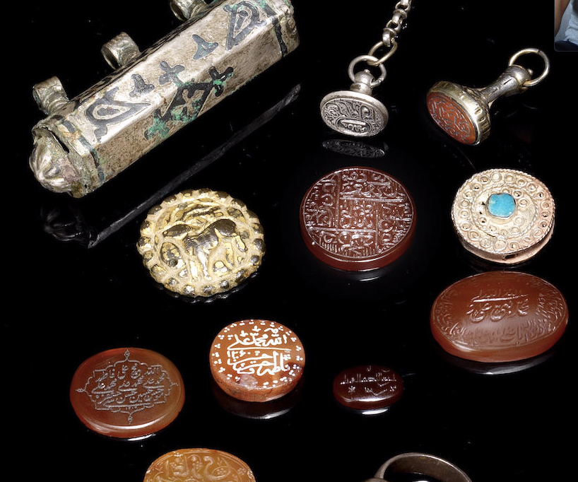A group of twelve Amulets, Pendants and Seals. Persia, 18th - 20th Century. Comprising a silver amulet case with three suspension loops; six carnelians, one carnelian-set silver ring; two silver seals, one set with carnelian; one turquoise-set silver pendant with circular motifs; one gilt bronze pendant depicting a quadruped in relief  the silver amulet case 7.3 cms. wide (12). Image: Bonhams