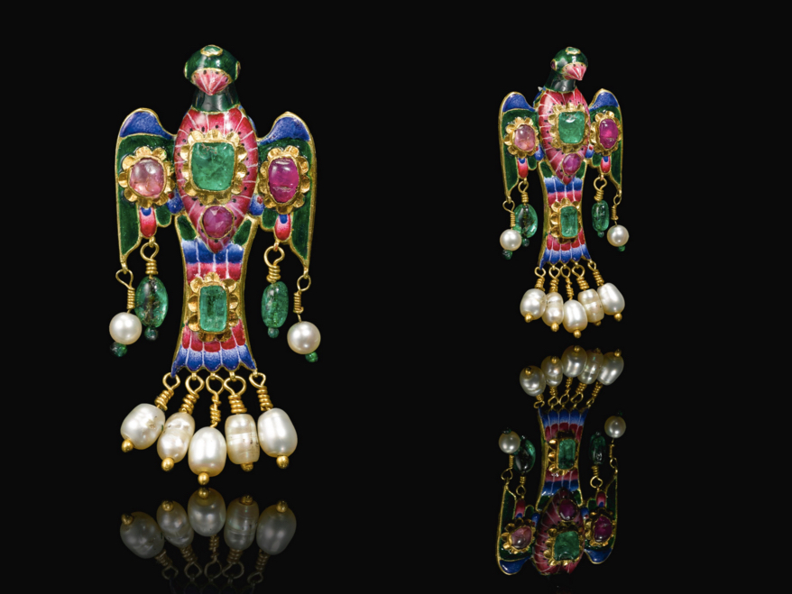 A Qajar gold, enamelled and gem-set eagle-form brooch, Persia, 19th century with wings outstretched, decorated throughout in polychrome enamels, set with emeralds and rubies, with pendant pearls suspended from the wings and tail by gold wire elements, fitted with a pin at the back. 7cm. Image: Sotheby's