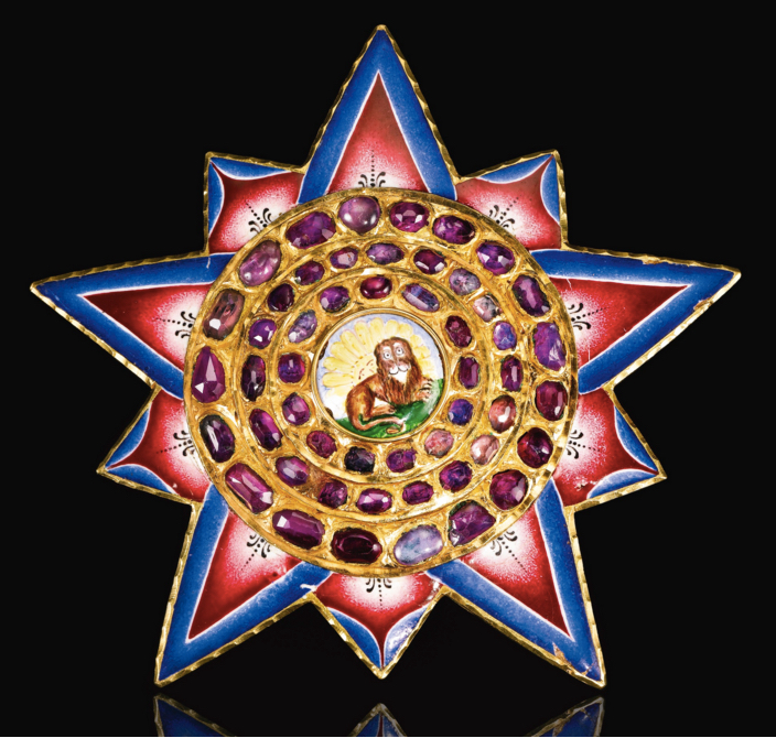 A gold, enamelled and jewelled insignia of the Qajar order of the Lion and Sun, Persia, early 19th century of stellar form with stepped gold frame set with rubies featuring an enamelled medallion with recumbent lion in front of a rising sun, the rays with gradated pink and blue bands, hinged pin for attaching to reverse. 9cm. Image: Sotheby's