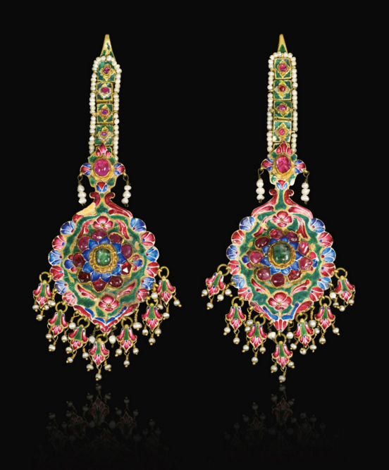 A pair of large Qajar gold, enamelled and jewelled earrings/hair pendants, Persia, 19th century. Each polychrome enamelled pendant set with a central gem-set flowerhead including rubies and emeralds, with hanging palmettes and seed-pearls, surmounted by a linked chain decorated with enamelled flowers and gem-set within a seed-pearl border, the reverse with ornate bird and floral design. Image: Sotheby's