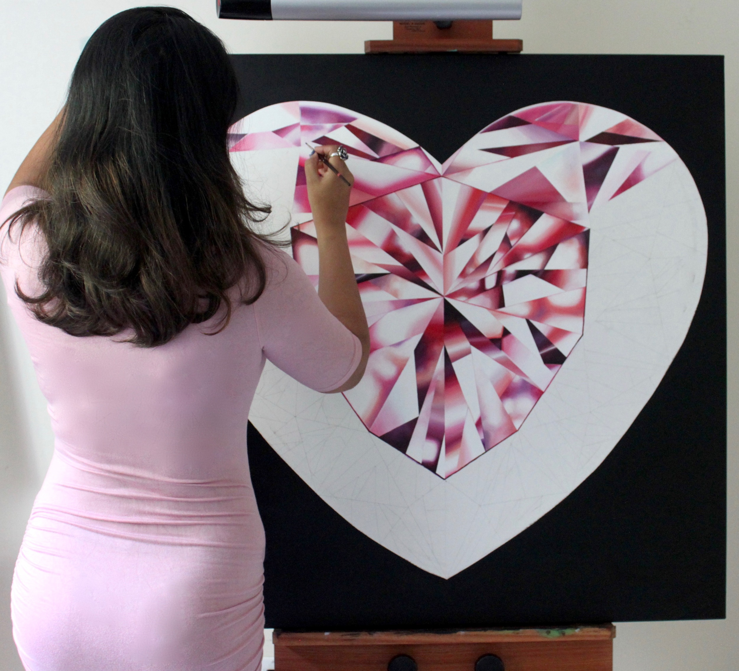 Reena Ahluwalia at her studio working on the 'Passionate Heart' - Portrait of a Pink Heart-Shaped Diamond. 36 x 36 inches. Acrylic on Canvas. ©Reena Ahluwalia
