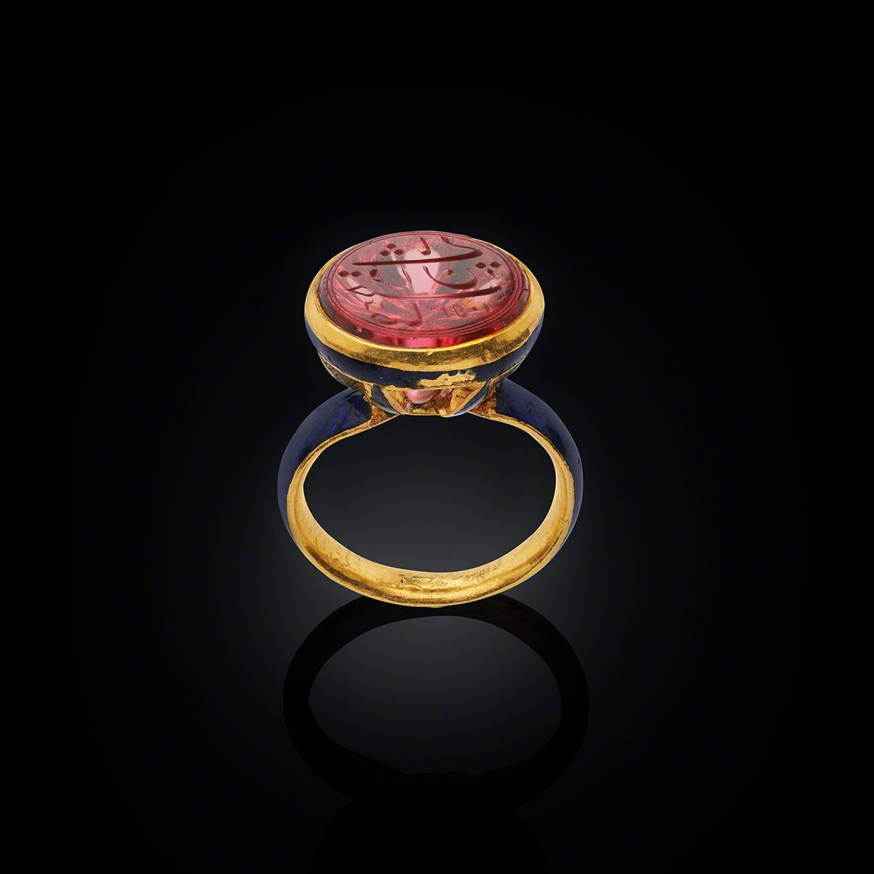 "Ring with Shah Jahan's Spinel    North India, the spinel dated AH 1053 (AD 1643– 44); the ring, c. 1900Gold with enamel, the spinel inscribed in Persian: Sahib qiran-i thani (""Second Lord of the Auspicious Conjunction"")    Dating from 1643, this spinel is engraved on the reverse ""Sahib qiran-I thani"" which translates as ""Second Lord of the Auspicious Conjunction"", the title of Emperor Shah Jahan who ruled 1628 - 1658. The title was chosen by Shah Jahan himself in reference to Timur (Tamerlane), the Mughals' dynastic ancestor, who bore the title ""Lord of the Auspicious Conjunction"". It is most likely that the engraving on the spinel was also the sovereign's personal seal. Image courtesy: © The Al Thani Collection"