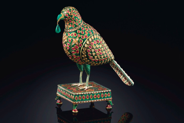An enamelled and gem set model of a parrot, Hyderabad, Deccan, circa 1775-1825. Set with diamonds, rubies and emeralds and with a pendant emerald hanging from its beak, on a stand similarly decorated, base decorated with two central flowers in green and white enamel and four leaves in each corner. Image: Christie's