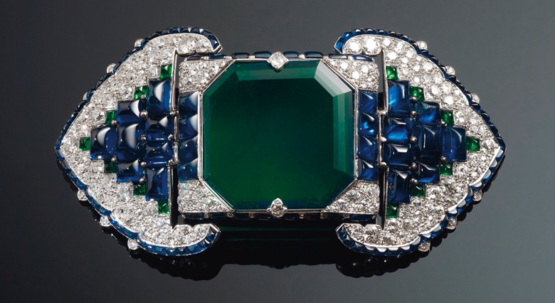 An Art Deco emerald, sapphire and diamond belt buckle-brooch, Cartier. Octagonal step-cut emerald of 38.71 carats, buff-top calibré-cut sapphires and emeralds, old and single-cut diamonds, platinum and 18k white gold. Many of Cartier's finest jewels from this period were inspired by Indian architecture, gems and jewels. The calibré-cut sapphire trim and diamond detail are reminiscent of ornate archways present in Mughal palaces and royal quarters. Image: Christie's