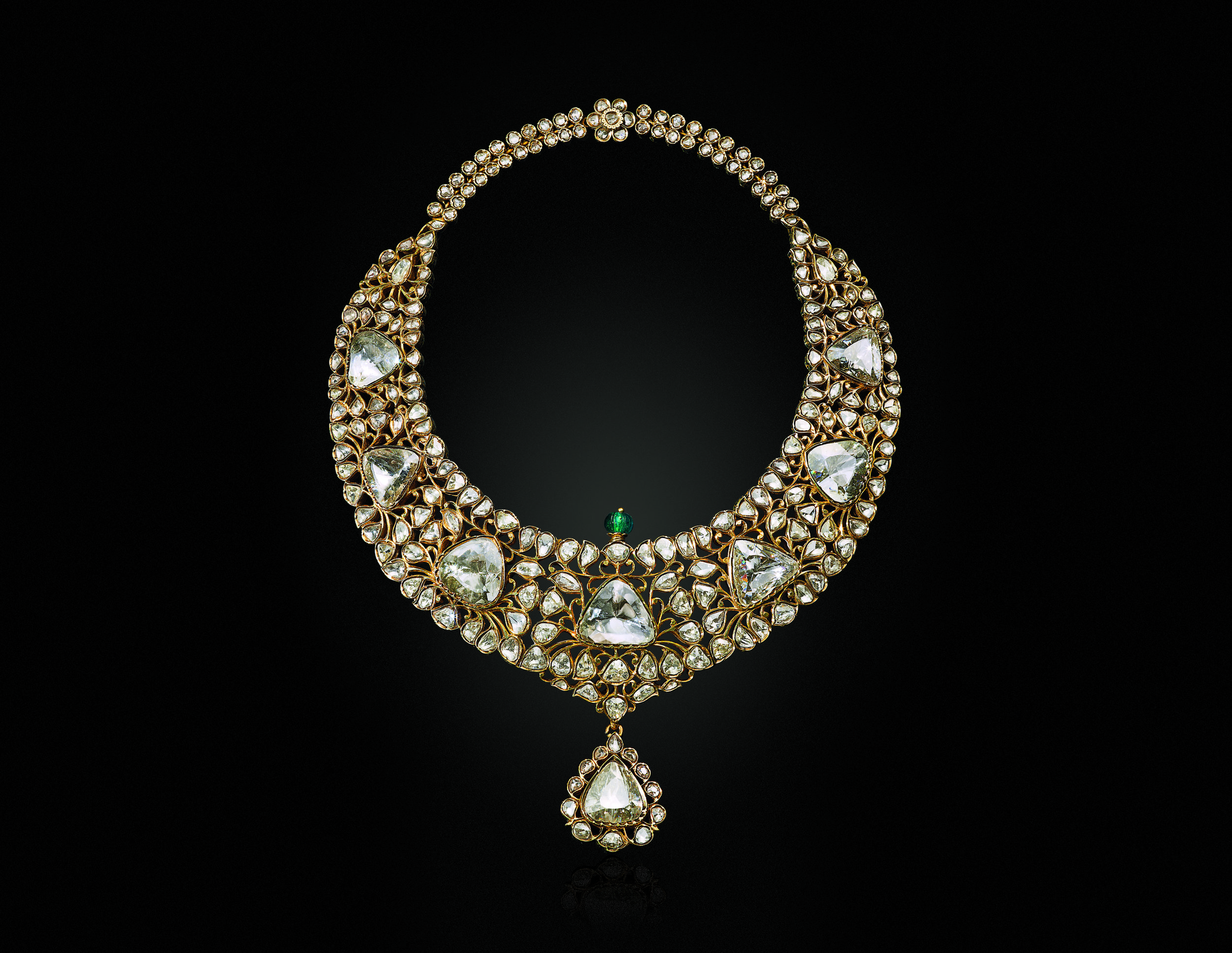 The Nizam of Hyderabad Necklace. Diamond, emerald and enamel necklace. The eight modified triangular-shaped table-cut golconda diamonds, variously-shaped faceted and rose-cut diamonds, carved emerald bead, green enamel, foil, gold, engraved on the reverse with foliate motif, 16 in, late 19th century. The modified brilliant-cut of these diamonds reflect the advancement of gem faceting in India. Additionally, the openwork setting and symmetrical nature of the necklace's design is the direct result of Western influence. Image: Christie's