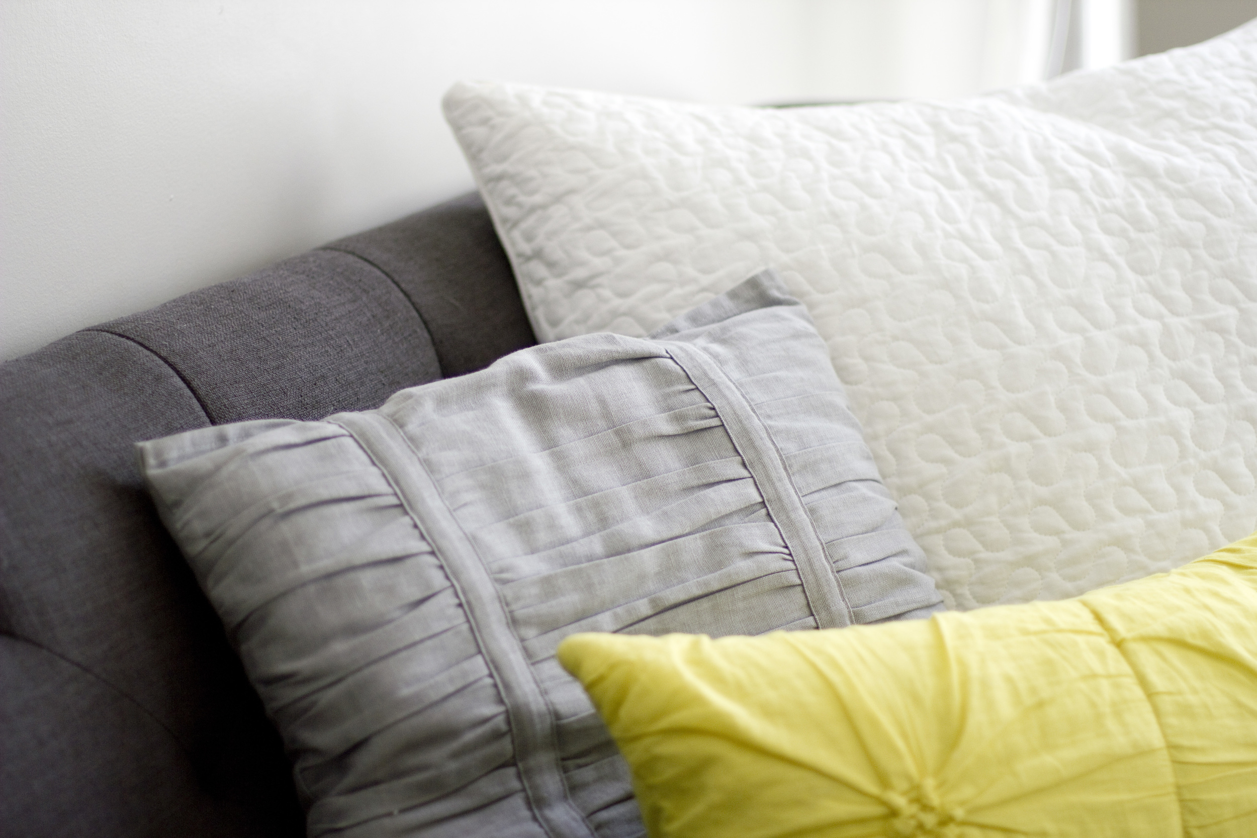 Pillows! White one was in theIKEA clearance bin, gray one was homemade from somecurtains. Yellow one was a sham cover from Target that I cut in half and sewedinto two pillows. I found some down inserts at Crate & Barrelthat were the exact size I needed. The insertswere only like $11 each, so it was very affordable.
