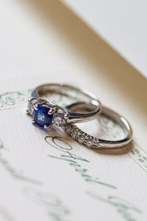 Sapphire and diamond engagement ring with diamond wedding band. On ecru wedding invitation.