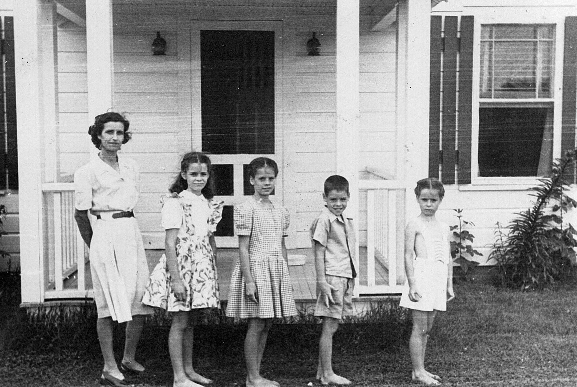Louella and her four children posed in front of the farm house