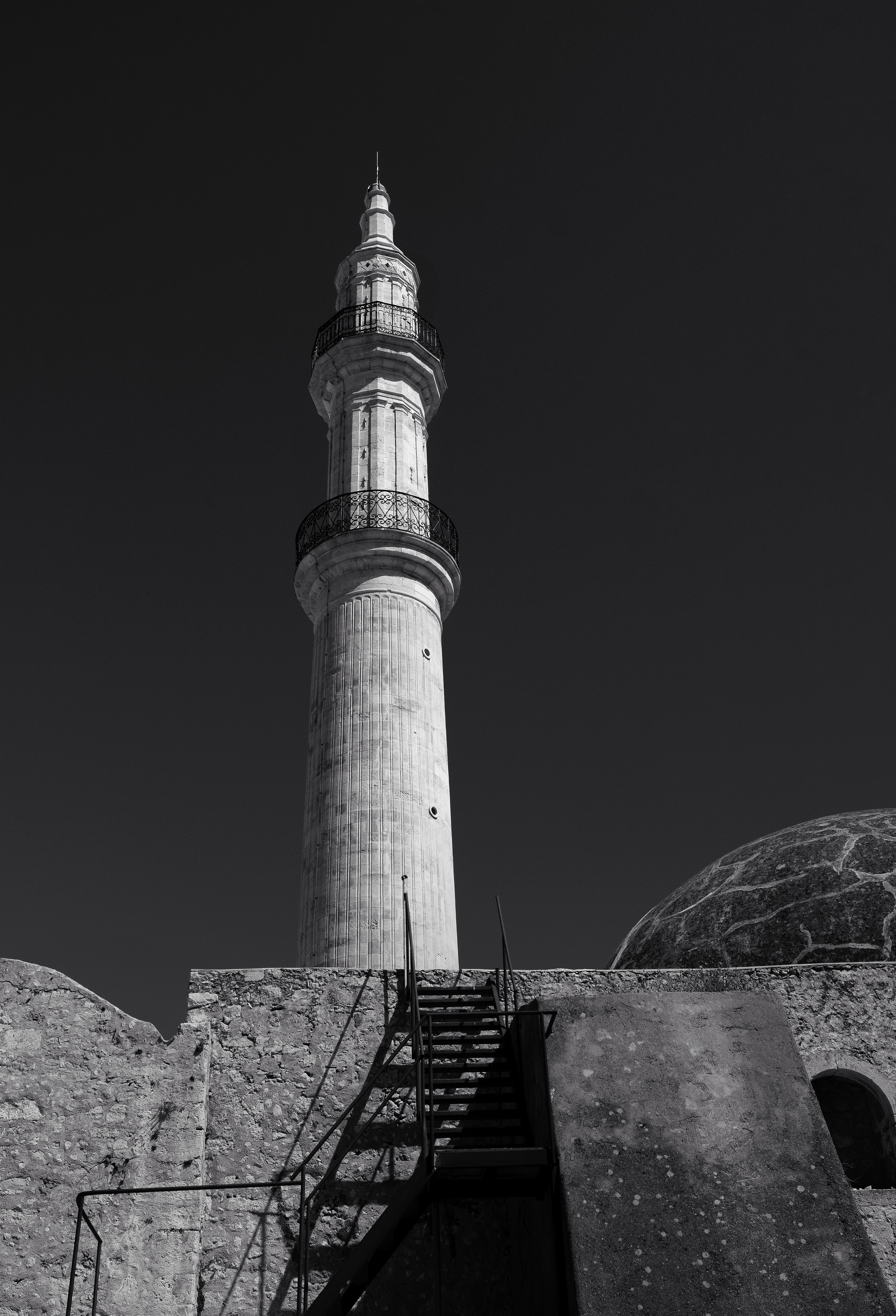 The afternoon sunlight emphasizes the orange colored stone of the Minaret