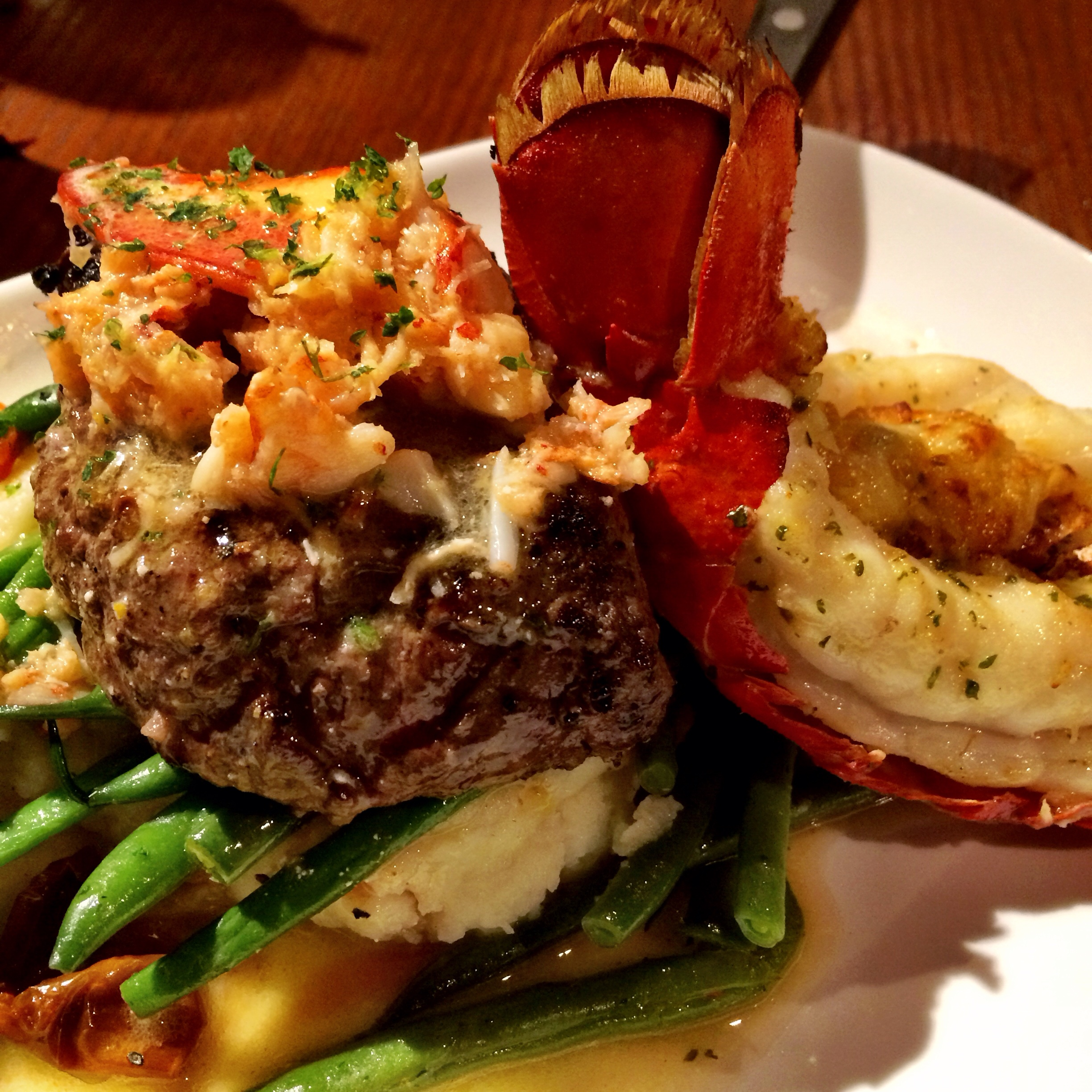Ultimate Surf and Turf. A Maine lobster tail baked with crab-and-seafood stuffing paired with a peppercorn-seasoned grilled sirloin topped with Maine lobster meat in a citrus-hollandaise sauce. Served over mashed potatoes, roasted tomatoes and green beans
