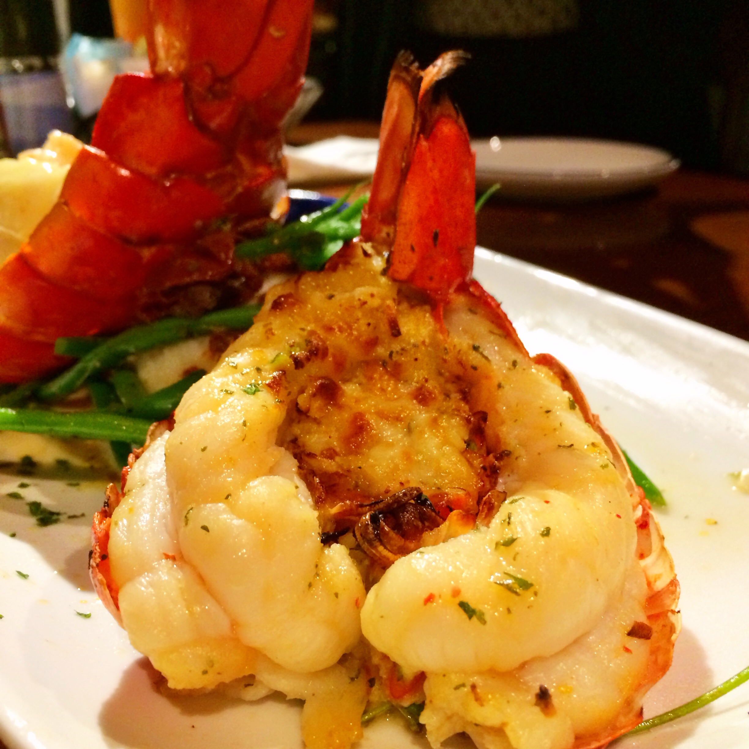Dueling Lobster Tails. A roasted Maine lobster tail topped with tender shrimp in a creamy garlic sauce paired with a golden-baked Maine lobster tail with crab-and-seafood stuffing. Served over mashed potatoes, roasted tomatoes and green beans