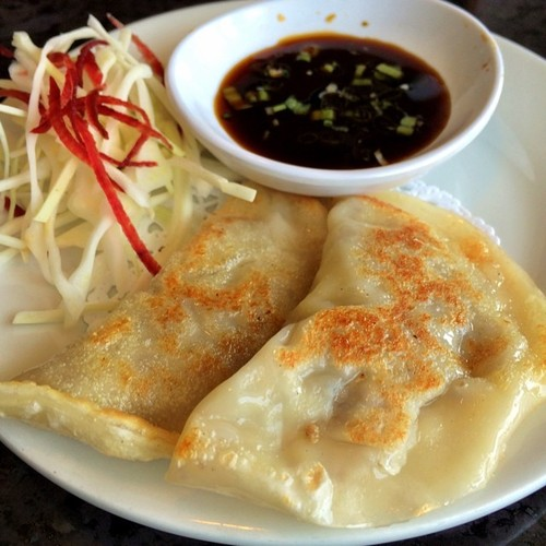 Pan-fried dumplings stuffed with sweet potato noodles, cabbage and beef, served with a side of soy vinaigrette