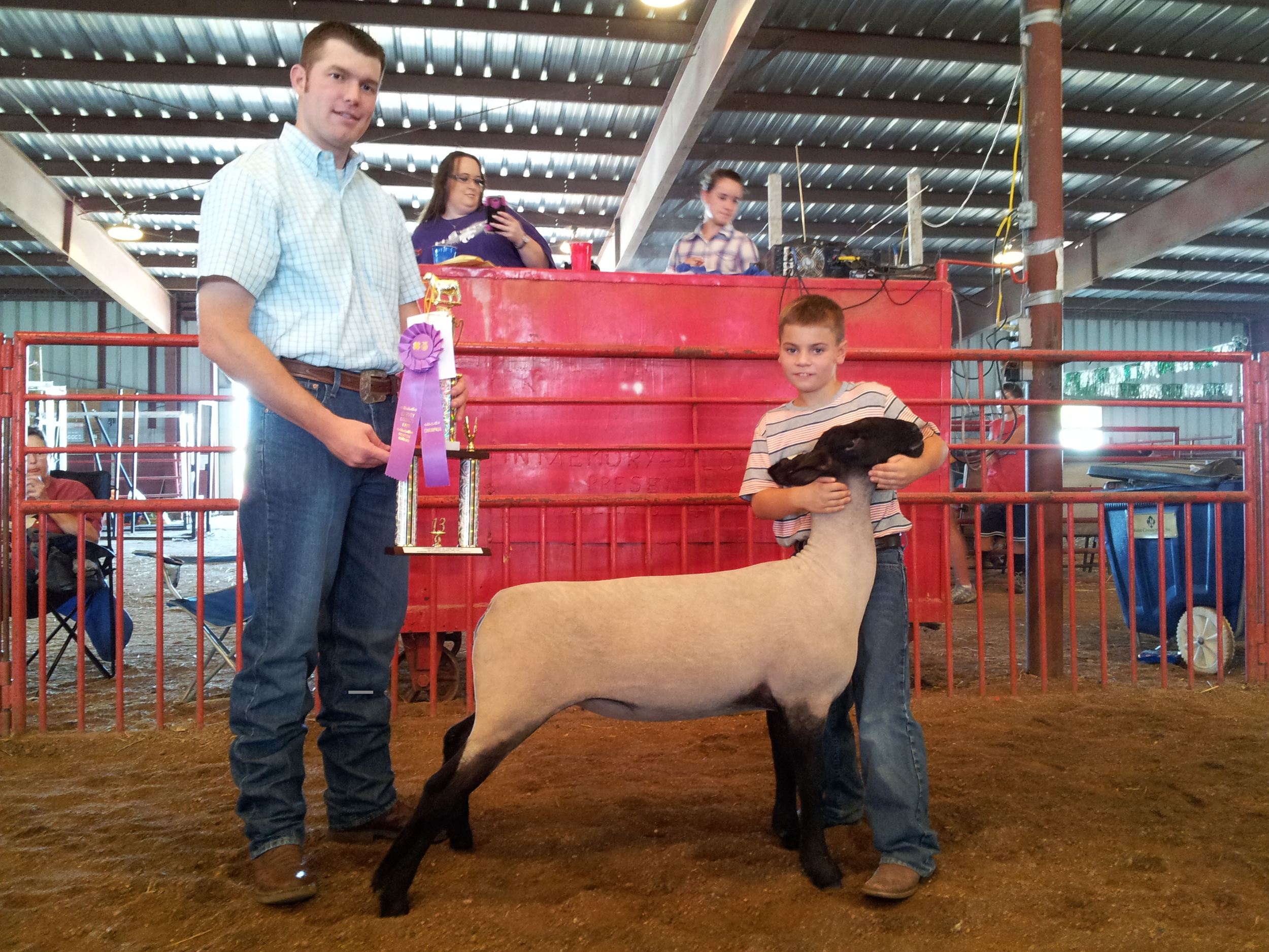 Nine-year-old Clayton poses with his championship breeding ewe at the Harvey County, Kansas, fair. He won two championships that day.