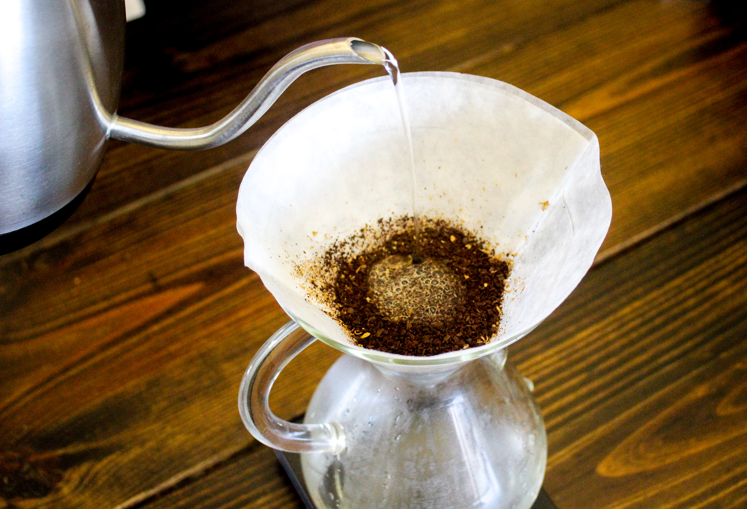 3. Place Chemex on scale and zero out.Begin by pouring a small amount of water (3-4 tablespoons) on the grounds. This is the bloom phase. A gooseneck kettle makes the pouring process much easier. Wait 30-45 seconds before continuing your pour.