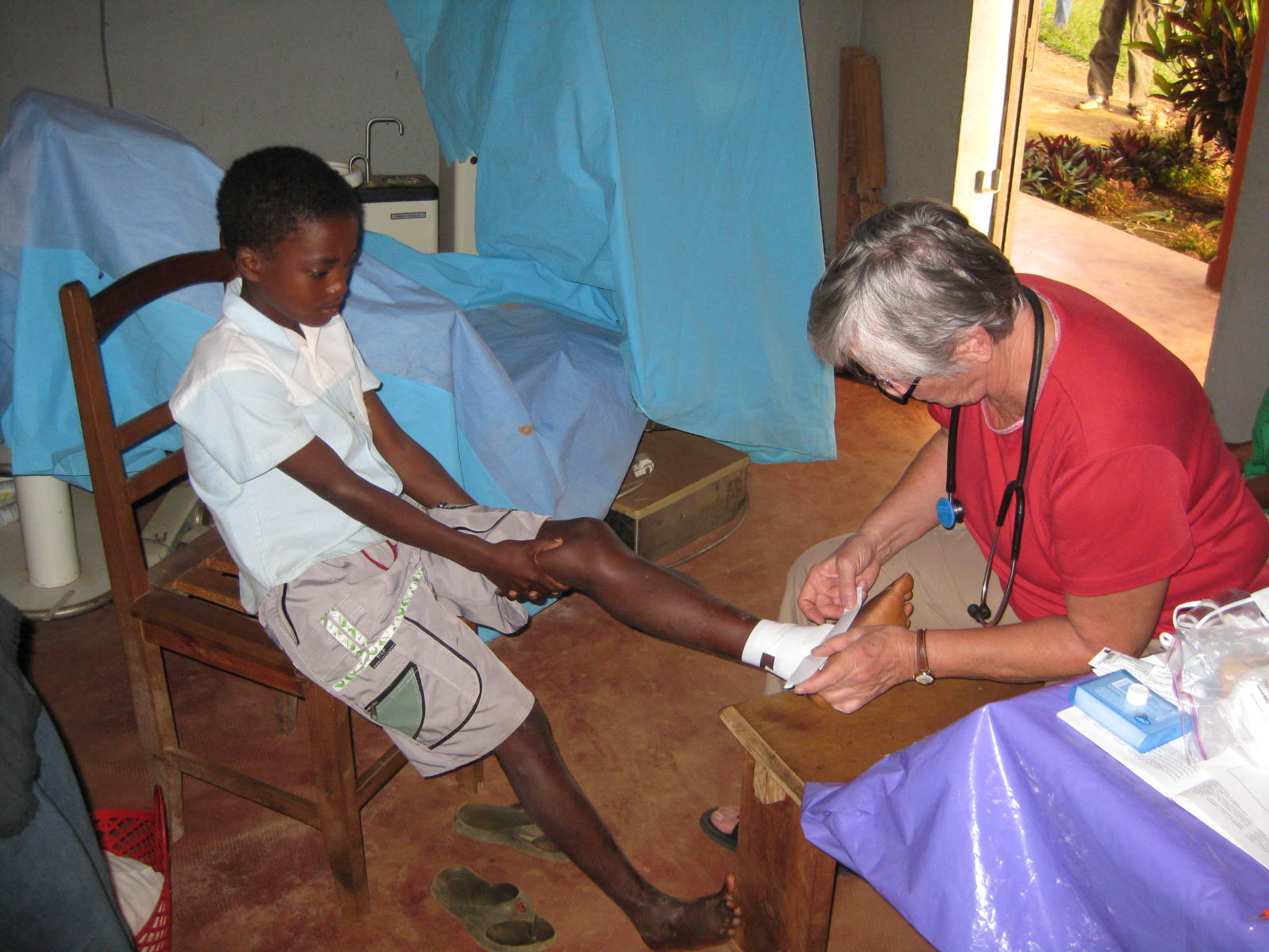 Cass treating a young boy's infected foot. Note how well-dressed andscrubbed the child is. Though poor, families have much pride in presentingthemselves and children to the western medical team.