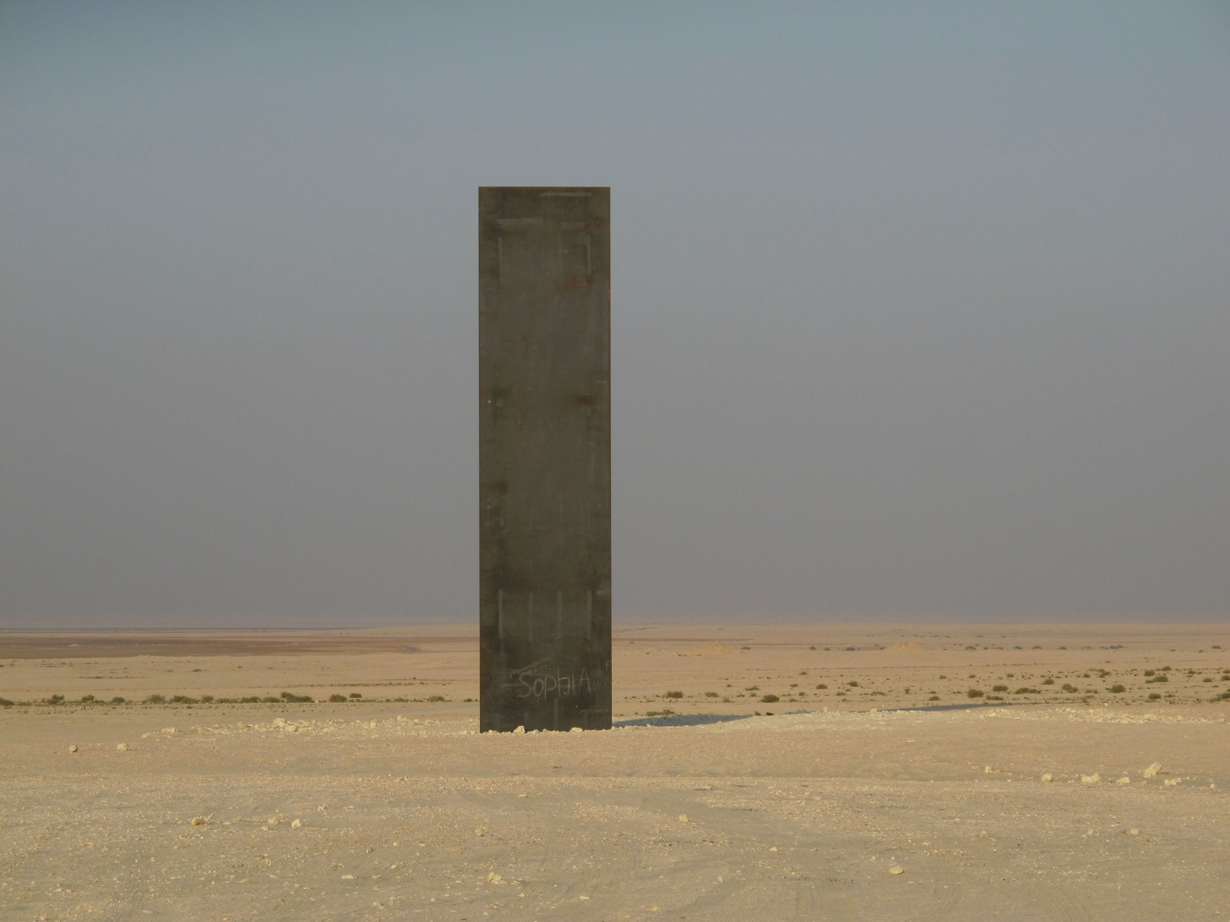 One of the four steel plates standing in a line in the Qatari desert