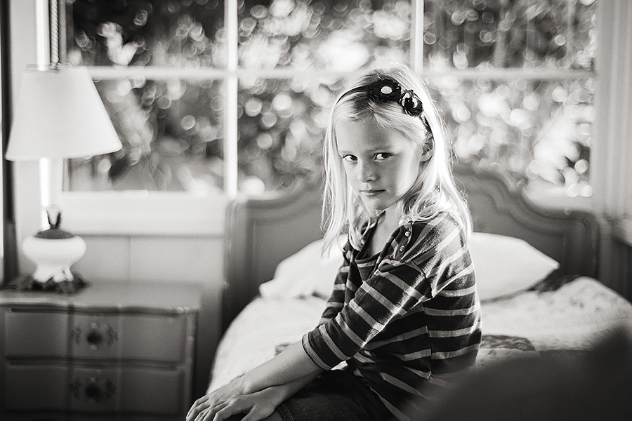 This portrait of Jorryn, made with a 50mm f1.4 Zeiss lens was shot at f2 and again shows the signature highlights or bokeh that I have come to love with the Zeiss branded lenses. And, because it's a 50mm focal length there's enough detail of the scene (here showing one of the historic Crystal Cove cottages where the family was vacationing).