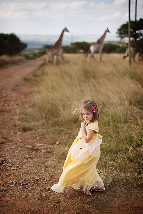 """Still one of my favorite portraits of my daughter Kate made to date (even though she is WAY beyond the """"Princess stage"""". Shot in Africa (while visiting family) we were at a game reserve and those are giraffes in the distance. Shot with the Zeiss 50mm f1.4 again at f2 there's the right amount of sharpness and out of focus elements to give the photograph an interesting look. I call this one """"Beauty and the Beasts"""" and it's even more special because her Granny Moira handmade the Belle dress for her."""