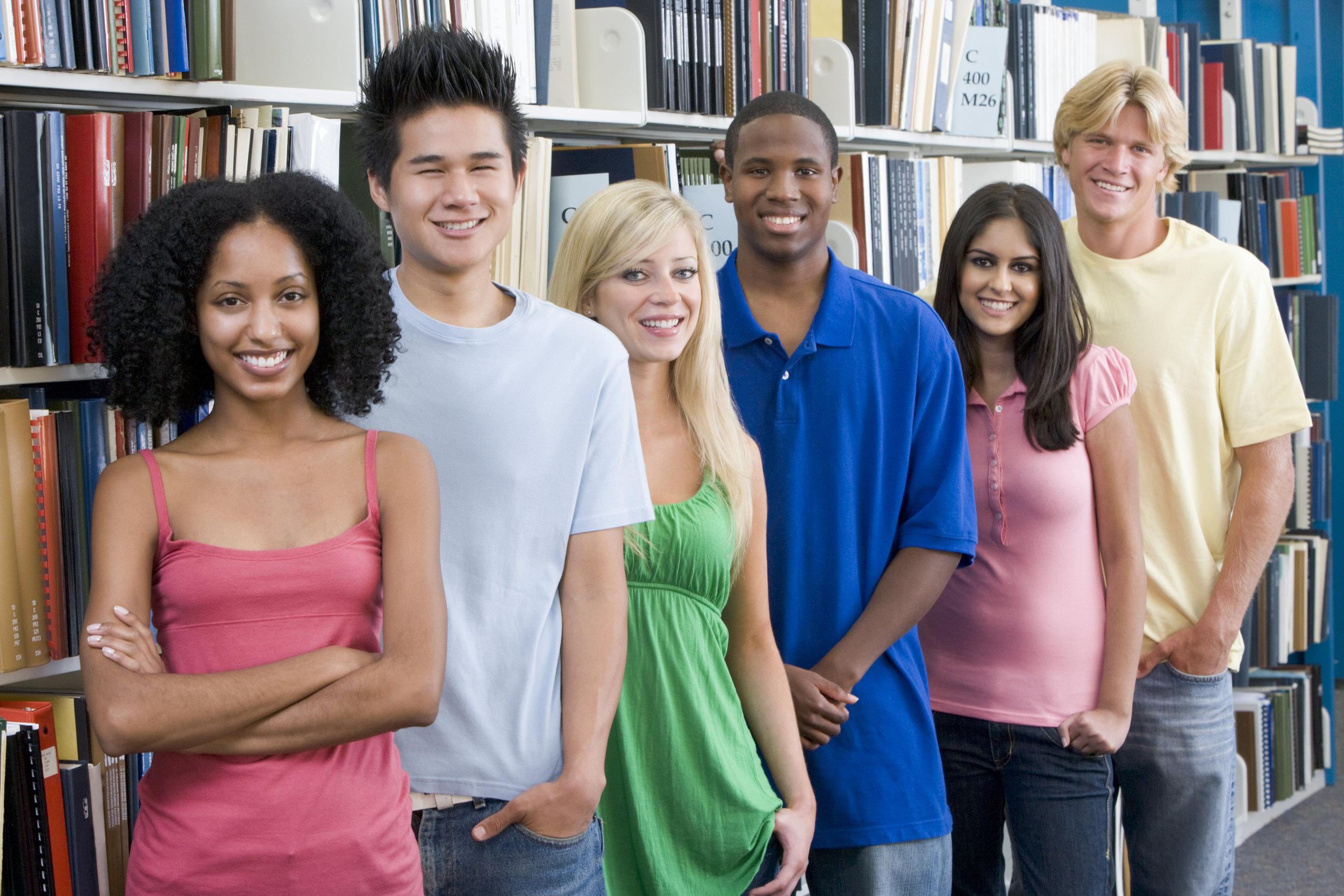 group-of-six-students-standing-in-front-of-library-bookshelves_HKoBzHASo.jpg