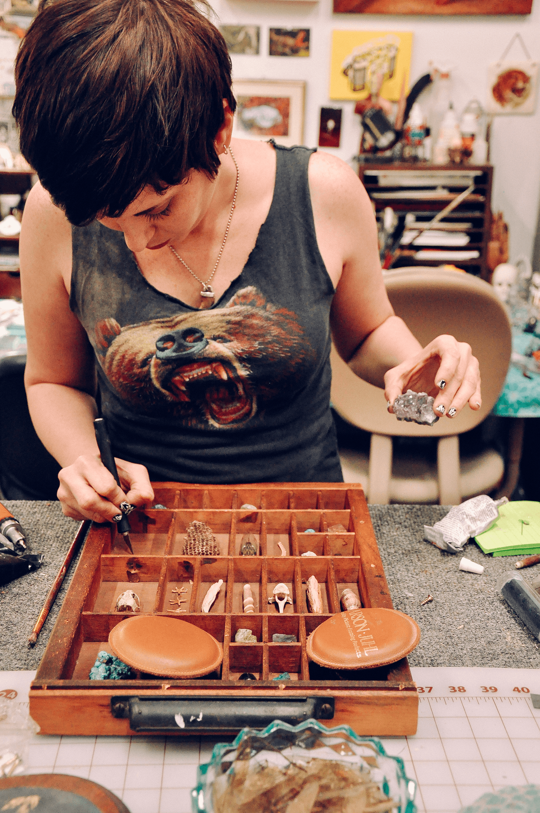Crystal hard at work in her studio as she carefully places objects in an antique letterpress draw.