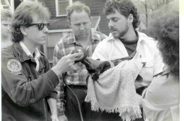 Bob Arnold (left) and Jon Oates (right) resuscitate a dog removed from a house fire on School Street in Weymouth, circa 1989. (Photo courtesy Jeff Parr)