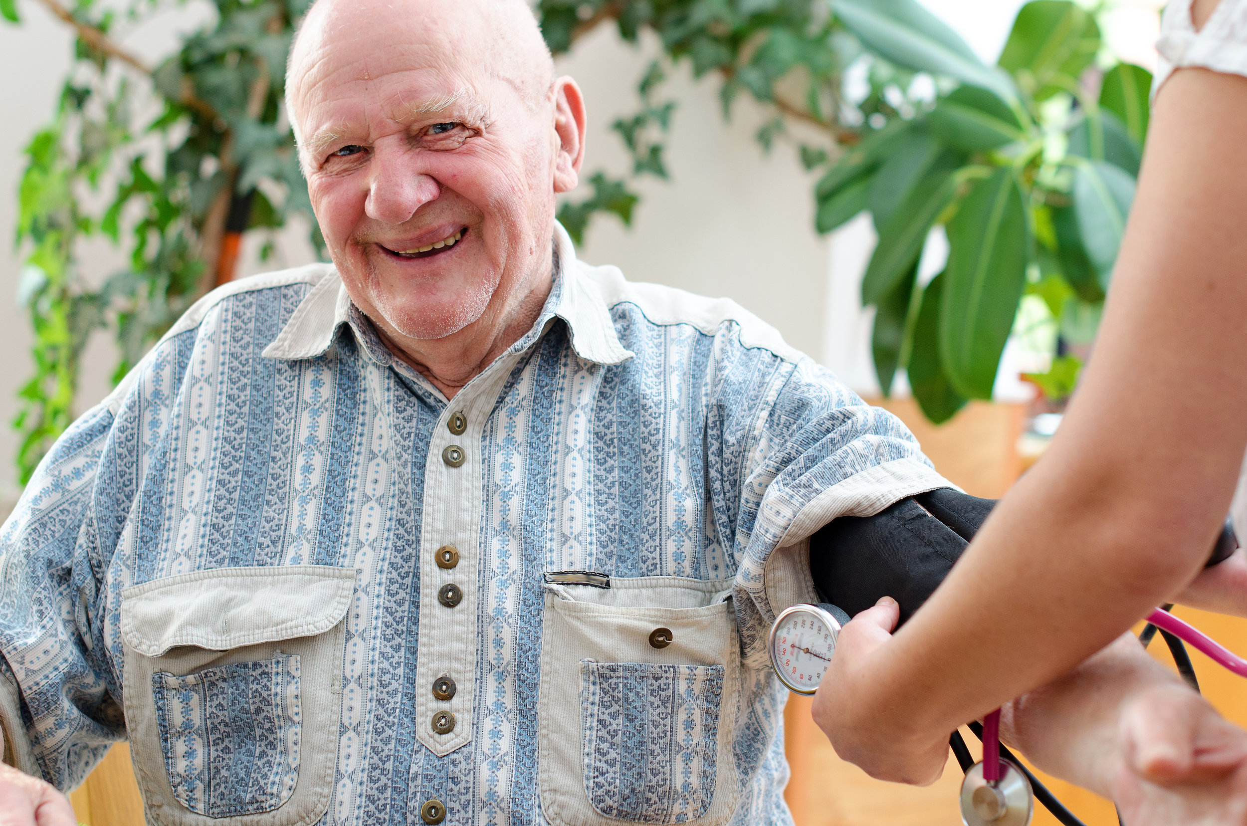 Man receiving blood pressure check at home